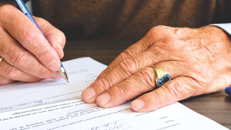 Älterer Mann unterschreibt Vertrag